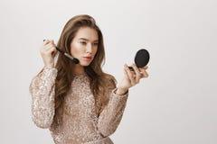 Modelo europeu adulto atrativo sensual no vestido formal luxuoso, mantendo o espelho disponivel e aplicando a composição com esco Fotos de Stock