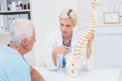 Modelo explaning de la espina dorsal del doctor al paciente mayor Fotografía de archivo libre de regalías