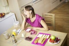 Modelo fêmea de Beauitful que boceja durante o pequeno almoço Foto de Stock Royalty Free