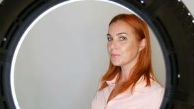 Modelo fêmea de meia idade adulto ruivo bonito que levanta na frente da câmera no estúdio vídeos de arquivo