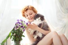Modelo fêmea encaracolado redhaired bonito com gato cinzento Fotografia de Stock Royalty Free