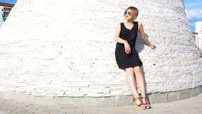 Modelo fêmea novo elegante à moda nos óculos de sol em um possing preto do vestido exterior video estoque
