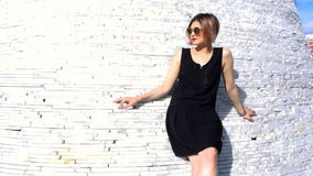 Modelo fêmea novo elegante à moda nos óculos de sol em um possing preto do vestido exterior filme