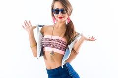 Modelo fêmea novo que está lateralmente, dobrando seu corpo, pondo o braço sobre o quadril, óculos de sol vestindo e acessórios b foto de stock royalty free