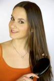Modelo fêmea que escova o cabelo triguenho longo Fotos de Stock Royalty Free
