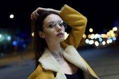 Modelo fêmea que levanta no revestimento amarelo e nos vidros grandes, leves por luzes do centro de cidade Womenswear à moda imagem de stock