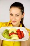 Modelo fêmea triguenho que mostra a fruta fresca Fotografia de Stock