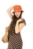 Modelo femenino adolescente que lleva un sombrero anaranjado y un dre marrón del lunar Fotografía de archivo libre de regalías