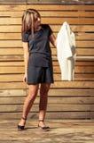 Modelo femenino adorable que comprueba la chaqueta blanca en el tiroteo de foto Imagen de archivo libre de regalías