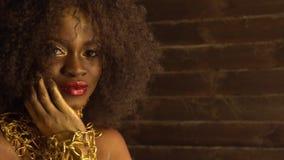 Modelo femenino afroamericano joven hermoso con maquillaje brillante del oro Arte de la cara Fondo negro del estudio metrajes