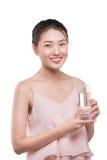 Modelo femenino asiático sonriente que sostiene el vidrio transparente en su mano Imagen de archivo