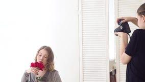 Modelo femenino atractivo que sostiene la flor roja en el fondo blanco media Fotografía romántica y apacible con la mujer linda metrajes