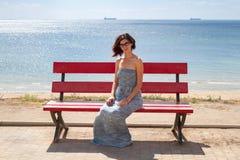 Modelo femenino caucásico joven que se sienta en un banco rojo En la playa y el mar del fondo Fotografía de archivo libre de regalías