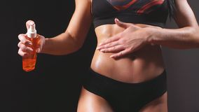 Modelo femenino de la aptitud apta de la mujer que aplica la loción hidratante de la grasa natural de la piel Muchacha en ropa in almacen de metraje de vídeo