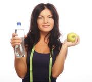 Modelo femenino de la aptitud que sostiene una botella de agua y una manzana verde Imágenes de archivo libres de regalías