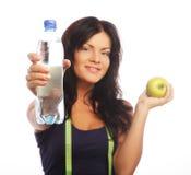 Modelo femenino de la aptitud que sostiene una botella de agua y una manzana verde Fotografía de archivo