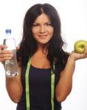 Modelo femenino de la aptitud que sostiene una botella de agua y una manzana verde Fotografía de archivo libre de regalías