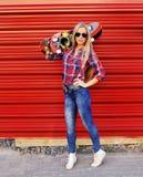 Modelo femenino de moda con el monopatín que presenta en una pared roja Imagen de archivo