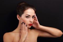 Modelo femenino del maquillaje atractivo que presenta con el lápiz labial rojo en negro Imagen de archivo