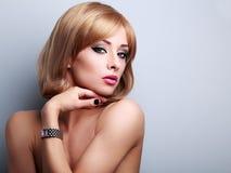 Modelo femenino del maquillaje rubio hermoso que presenta en los relojes de moda o Fotografía de archivo libre de regalías