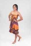 Modelo femenino del moreno hermoso en el vestido sin tirantes que presenta en los vagos blancos Imágenes de archivo libres de regalías