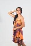 Modelo femenino del moreno hermoso en el vestido sin tirantes que presenta en los vagos blancos Imagenes de archivo