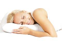 Modelo femenino del pelo ligero, sonriendo y mintiendo en la almohada Imagenes de archivo