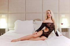 Modelo femenino en la cama suave blanca imagenes de archivo
