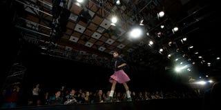 Modelo femenino en un desfile de moda en la prolongación del andén (Rus