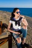 Modelo femenino encantador que presenta para la cámara contra el mar Fotos de archivo