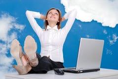 Modelo femenino feliz con las piernas en el escritorio imagen de archivo libre de regalías