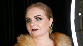 Modelo femenino gordo con maquillaje de oro y ojos ahumados en una capa de la piel de zorro y de los pendientes de oro grandes qu almacen de video