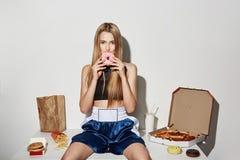 Modelo femenino hermoso alegre con el pelo rubio en el desgaste del deporte que se sienta en la tabla, comiendo la comida basura, Fotos de archivo