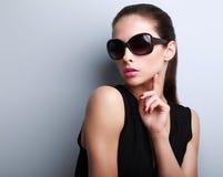 Modelo femenino hermoso elegante atractivo en la presentación de las gafas de sol de la moda foto de archivo