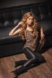 Modelo femenino hermoso en la moda con los tacones altos que se sientan en la ropa de cuero del leopardo del piso que lleva Fotografía de archivo