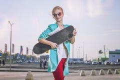 Modelo femenino hermoso en ropa casual con un monopatín Imagen de archivo libre de regalías