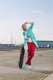 Modelo femenino hermoso en ropa casual con un monopatín Fotos de archivo libres de regalías