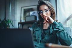 Modelo femenino hermoso joven que se sienta en la butaca c?moda y que usa el ordenador port?til Proceso de trabajo en coworking fotografía de archivo libre de regalías