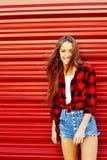 Modelo femenino hermoso precioso de risa feliz que presenta en la pared roja Fotografía de archivo