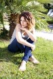 Modelo femenino hermoso que se sienta en parque Fotos de archivo libres de regalías