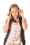 Modelo femenino joven con los vidrios amarillos que se pegan la lengua hacia fuera Imagen de archivo