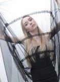 Modelo femenino joven hermoso que descansa en una butaca acogedora grande Fotografía de archivo libre de regalías
