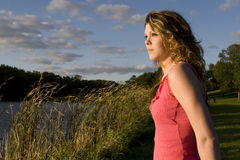 Modelo femenino lindo que presenta por un lago Imagen de archivo libre de regalías