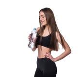 Modelo femenino positivo de la aptitud después del entrenamiento que sostiene una botella de agua pura sobre el fondo blanco Imágenes de archivo libres de regalías