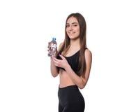 Modelo femenino positivo de la aptitud después del entrenamiento que sostiene una botella de agua pura sobre el fondo blanco Fotografía de archivo libre de regalías