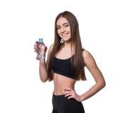 Modelo femenino positivo de la aptitud después del entrenamiento que sostiene una botella de agua pura sobre el fondo blanco Imagen de archivo