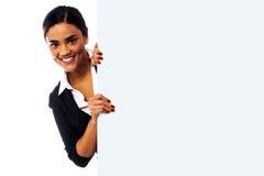Modelo femenino que lleva a cabo el tablero blanco en blanco del anuncio Imágenes de archivo libres de regalías