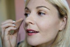 Modelo femenino rubio joven hermoso que aplica maquillaje Imagen de archivo libre de regalías