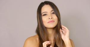 Modelo femenino sonriente que toca su pelo almacen de metraje de vídeo