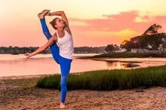 Modelo femenino Standing Split de la yoga en la playa Imagen de archivo
